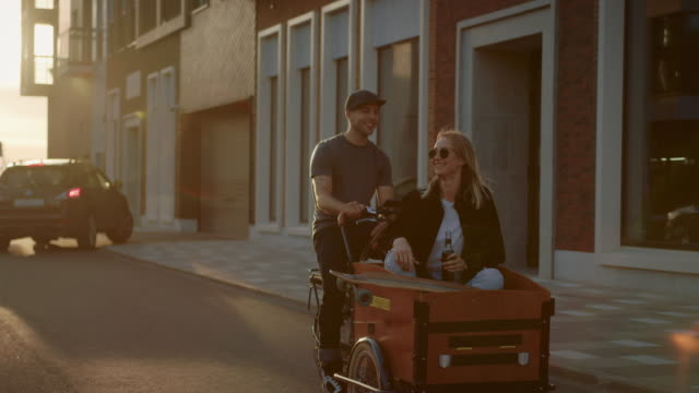 Handsome Young Man Rides on Adult Tricycle with Girlfriend Sitting in the Front Loading Trailer. Young Couple In Love Having Fun Together Riding Bicycle Through Fashionable City Street
