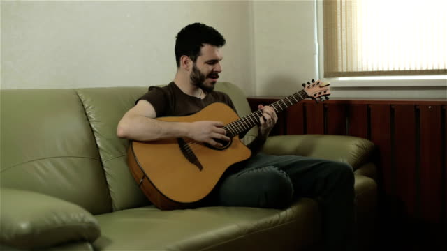 A handsome young man singing and playing the guitar. video
