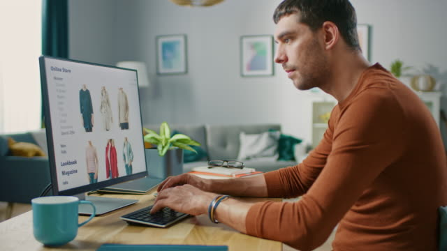 handsome young man sits at home browses through online retailer clothes selling store. man does online shopping for clothing items as a gift for his wife. - web video stock e b–roll