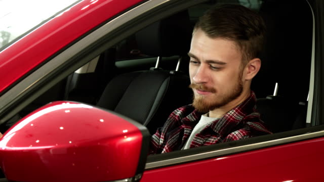 Handsome young man sitting comfortably in his new car smiling to the camera Handsome bearded young man sitting relaxed in his newly bought car smiling joyfully to the camera driving owner ownership consumerism buying shopping vehicle transport. car shopping stock videos & royalty-free footage