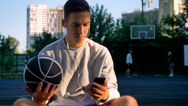 handsome young man sitting on basketball court and typing on phone, looking at camera, holding ball, people playing in background - sportowiec filmów i materiałów b-roll