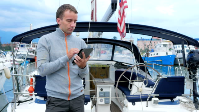 Handsome young man standing near his yacht. He checks messages on the tablet and meets friends in a social network Handsome young man standing near his yacht. He checks messages on the tablet and meets friends in a social network crank mechanism stock videos & royalty-free footage