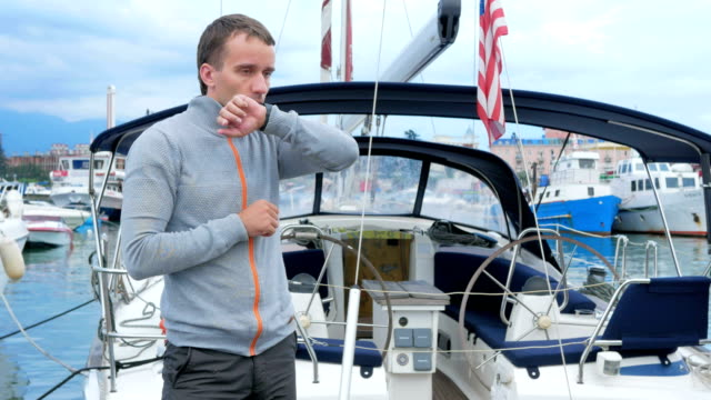Handsome young man standing near his yacht. He checks messages on the smart watch and meets friends in a social network Handsome young man standing near his yacht. He checks messages on the tablet and meets friends in a social network crank mechanism stock videos & royalty-free footage