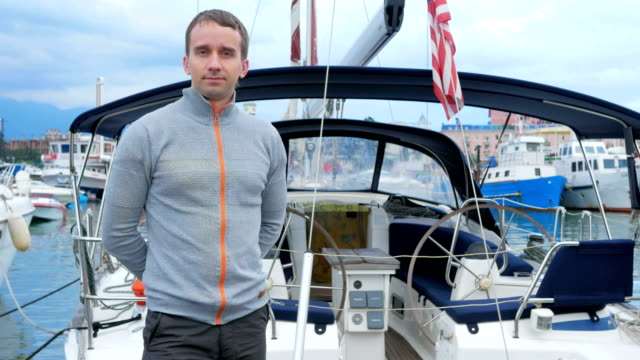 Handsome young man standing near his yacht. He looks into the camera Handsome young man standing near his yacht. He looks into the camera. crank mechanism stock videos & royalty-free footage