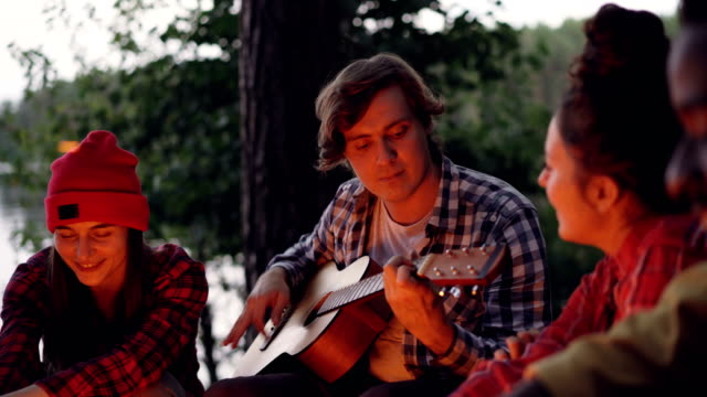 Handsome young man tourist is playing the guitar and smiling while his friends are singing and having fun resting around fire near lake or river. Green trees are visible. Handsome young man tourist is playing the guitar and smiling while his happy friends are singing and having fun resting around fire near lake or river. Green trees are visible. guitar stock videos & royalty-free footage