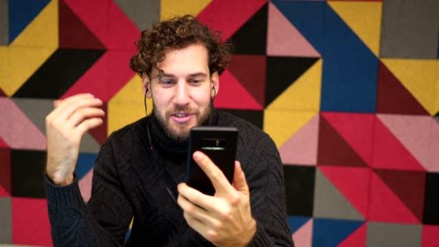 kahve molası sırasında sohbet yakışıklı genç video - kulak i̇çi kulaklık stok videoları ve detay görüntü çekimi