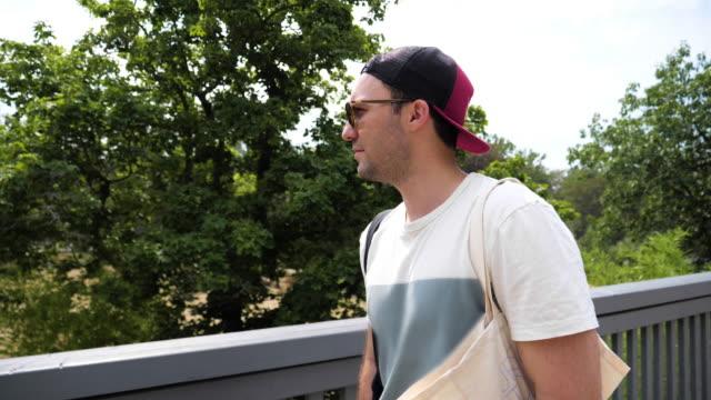 vídeos de stock, filmes e b-roll de jovem bonito andando no parque - boné
