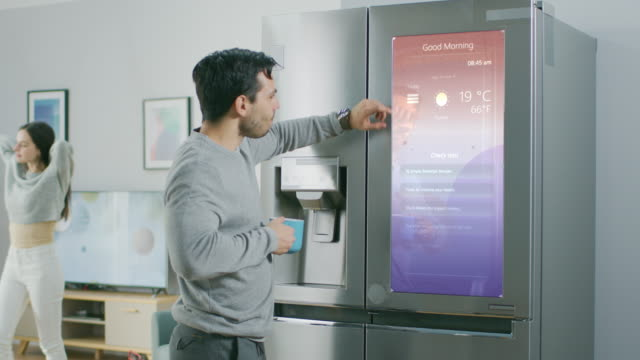 Handsome Young Man Walks Over to a Refrigerator While Drinking His Morning Coffee. He is Checking a To Do List on a Smart Fridge at Home. Kitchen is Bright and Cozy. Handsome Young Man Walks Over to a Refrigerator While Drinking His Morning Coffee. He is Checking a To Do List on a Smart Fridge at Home. Kitchen is Bright and Cozy. Shot on RED EPIC-W 8K Helium Cinema Camera. fridge stock videos & royalty-free footage