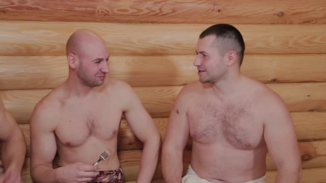 Handsome young men eating in a sauna and talking