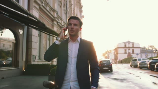 Handsome young stylish man talking on mobile phone outdoors with bicycle in city center during sunset