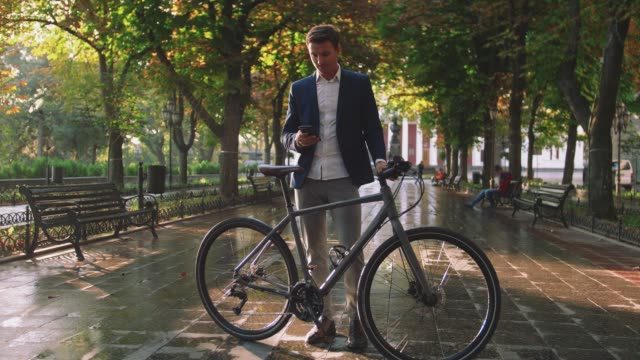 Handsome young stylish man using smartphone outdoors with bicycle in park in city center during sunset, slow motion, close up shot