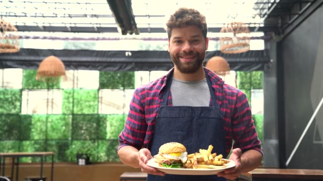 vídeos de stock e filmes b-roll de handsome young waiter holding an order of hamburger with fries showing it to camera smiling - hambúrguer comida