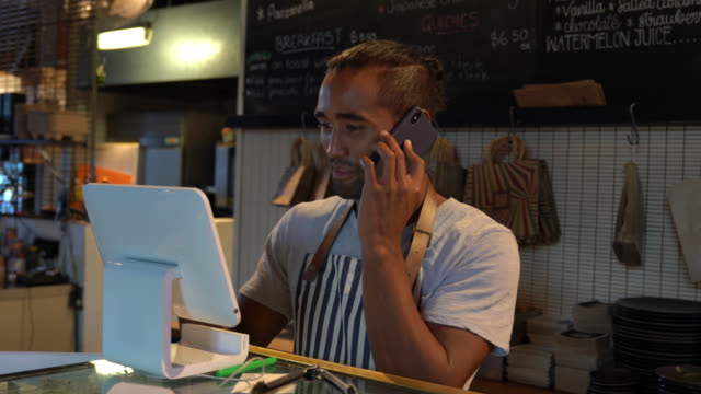 vídeos de stock e filmes b-roll de handsome young waiter registering a delivery on system while talking to customer on phone - encomendar
