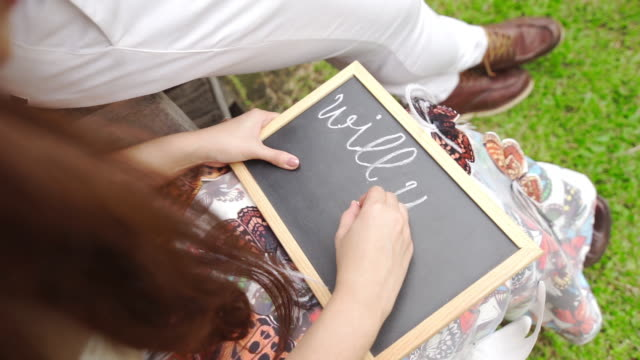 """Handwriting on a blackboard with the text """"Will you marry me question"""" written on it."""