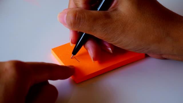 """handskrift ordet """"kom ihåg"""" på orange ett inlägg det papper eller anteckningar ark. motion 4k film - minne bildbanksvideor och videomaterial från bakom kulisserna"""
