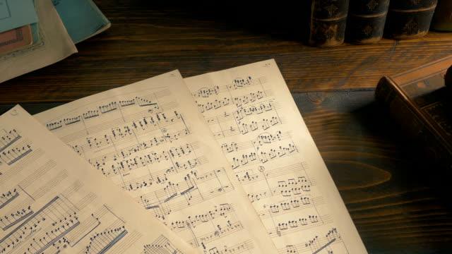 vídeos de stock e filmes b-roll de hand-written sheets of music on the table - compositor