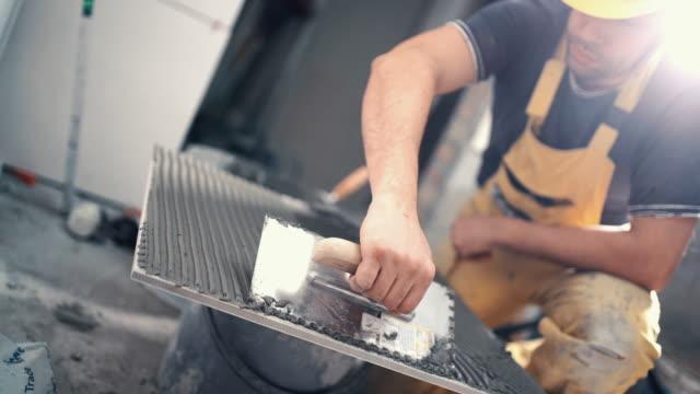 handyman tillämpa limmet på en bricka. - construction workwear floor bildbanksvideor och videomaterial från bakom kulisserna