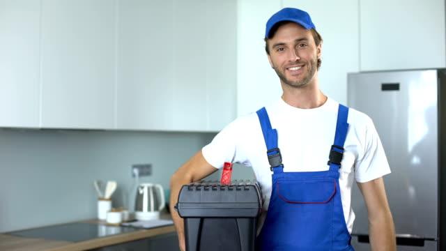 vídeos y material grabado en eventos de stock de handyman sosteniendo herramientas de pie en la cocina, servicios profesionales de fontanería - fontanero