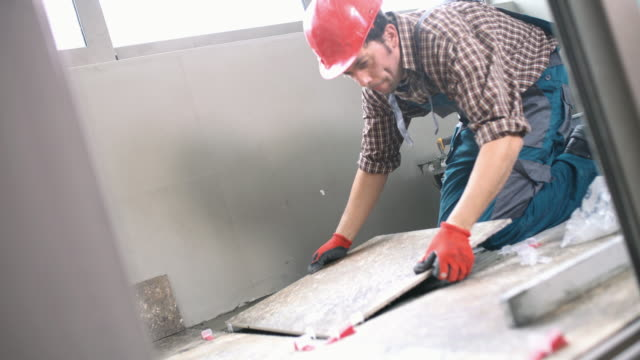 Handyman installing ceramic tiles. Closeup side view of a handyman installing ceramic tiles on the floor of a client's home.The worker is wearing red uniform and helmet. 4k video. tile stock videos & royalty-free footage