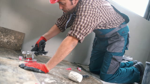 Handyman installing ceramic tiles. video