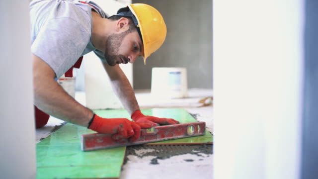 Handyman installing ceramic tiles. Closeup side view of a handyman installing green ceramic tiles over apartment floor. He's making sure if the tiles are perfectly aligned and horizontal. He's wearing red gloves and a yellow helmet. 4k video. tile stock videos & royalty-free footage