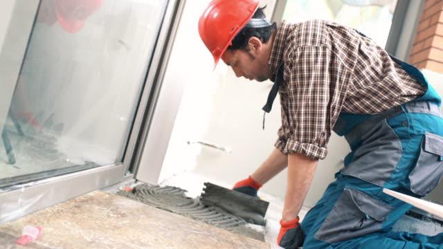 Handyman installing ceramic tiles. video