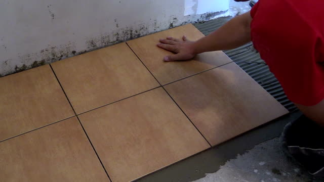 Handyman lay floor tiles at home. Closeup shot video
