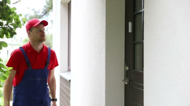 vidéos et rushes de réparateur de l'homme à tout faire à pied dans une maison de client avec la boîte à outils - uniforme