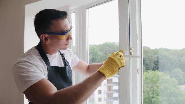 vídeos de stock e filmes b-roll de handyman using screwdriver to fix window handle, repair and installation services - obras em casa janelas