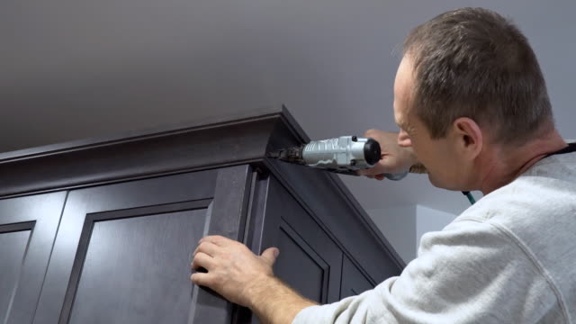 vídeos de stock e filmes b-roll de handyman working using brad nail air gun to crown moulding on white kitchen wall cabinets framing trim, with the all power tools - coroa