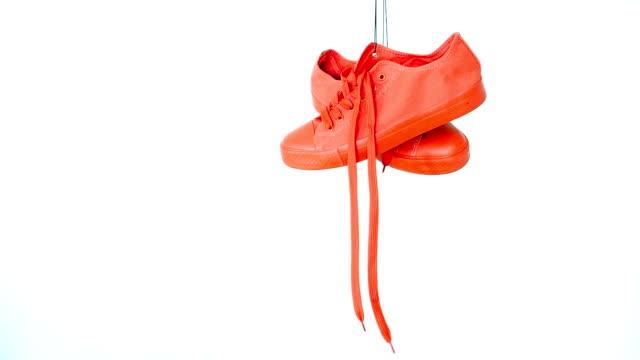ぶら下がり明るい色のスニーカー。ファッション女性トレンディトレーナー。スタイリッシュなヒップスタープリムソールブライトイエローコーラルカラースニーカー。ミニマルポップアー� - 吊るす点の映像素材/bロール