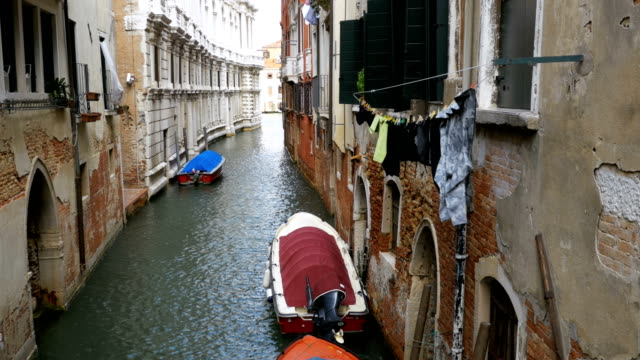 hanging clothes on the street after been washed in venice, italy - genova via del campo video stock e b–roll