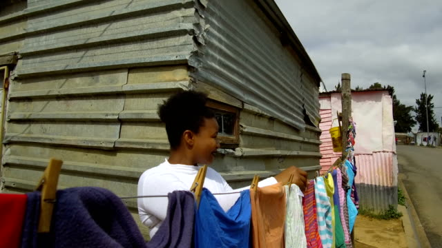 Hanging laundry in the Townships Woman hanging laundry in the Townships of South Africa western cape province stock videos & royalty-free footage