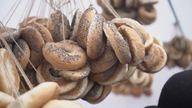 rotoli a forma di anello appesi in una tariffa in vendita su sfondo bianco, bagel, anello di pane con semi di papavero - fare video stock e b–roll