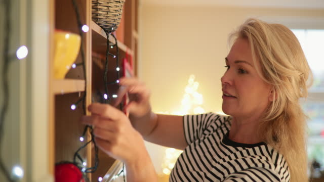 Hanging Up Fairy Lights Mature woman hanging up string lights in her kitchen at Christmas time. hanging stock videos & royalty-free footage