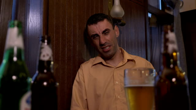 Hangover depressed man sitting at the bar after hard drinking video