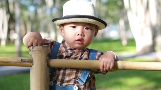 glück und niedlichen kleinen jungen spielen im freien - strohhut stock-videos und b-roll-filmmaterial