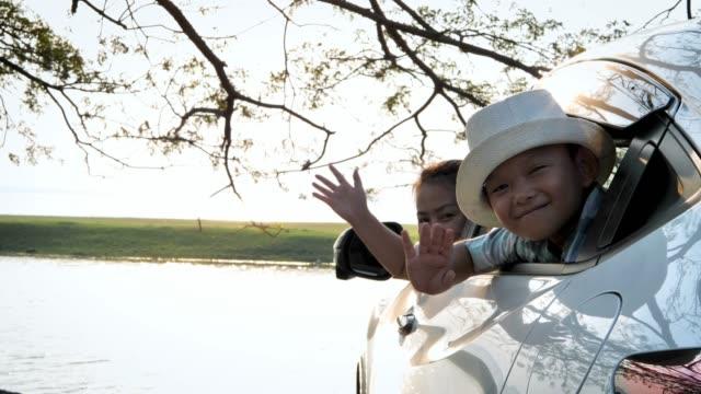 vidéos et rushes de bonheur famille asiatique mère et garçon sont agitant les mains se déplacent en voiture. fond naturel et le soleil du soir. ralenti - homme faire coucou voiture