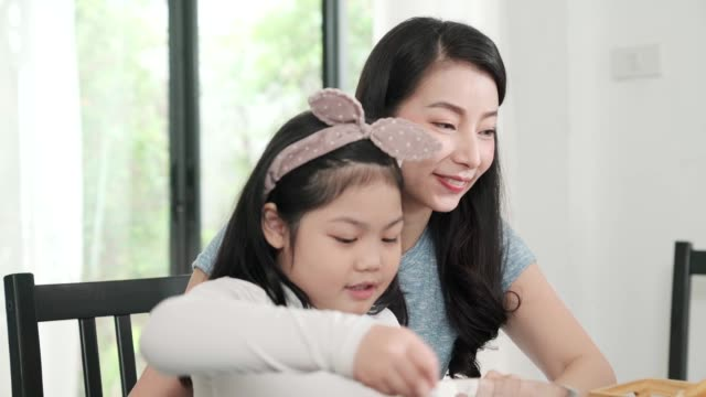 Happiness Asian Japanese family  breakfast at home. young parent and daughter eat cereal drink orange juice on table in the kitchen morning daylight.quality moment bonding family ideas concept