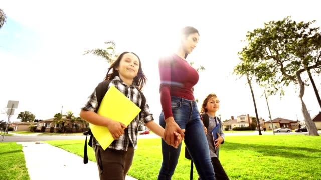 vídeos y material grabado en eventos de stock de familia de la felicidad caminando en el parque después de la escuela - madre e hijos
