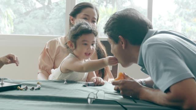 happiness: granddaughter feeding snack to grandfather - cultura orientale video stock e b–roll