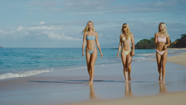 Happiness is enjoying the beach with friends Three beautiful blonde girls walking on the beach in slow motion, baywatch summer theme bikini stock videos & royalty-free footage