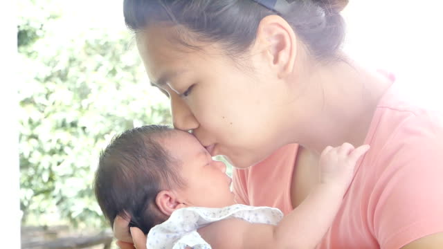 Happiness mother and baby kissing. Talking and resting together. Concept of happy family desire in no noisy home and carefree video