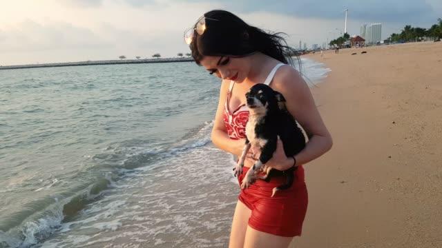 vidéos et rushes de femme de bonheur et un beau crabot ayant le bon temps sur la plage au coucher du soleil ensemble - prise avec un appareil mobile