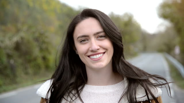 Happiness young woman portrait Close-up of dark hair happiness young woman smiling and looking at camera outdoors. Road in the background. front view stock videos & royalty-free footage