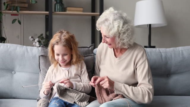 Happy 2 generations family grandmother and granddaughter knitting together
