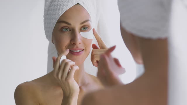 Happy 30s woman apply eye patches looking in bathroom mirror Happy attractive 30s woman apply eye care patches looking in bathroom mirror, healthy beautiful adult lady put undereye face skin care moisturizing pads for dark circles bags spa treatment concept bathroom stock videos & royalty-free footage