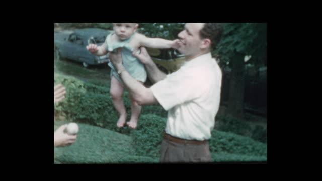幸せな 50 のママとパパが赤ちゃんを投げる - 古風点の映像素材/bロール
