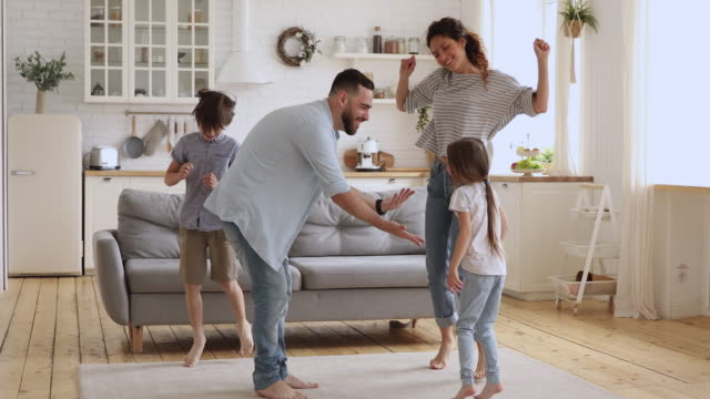 Happy active parents and children jumping dancing together in kitchen