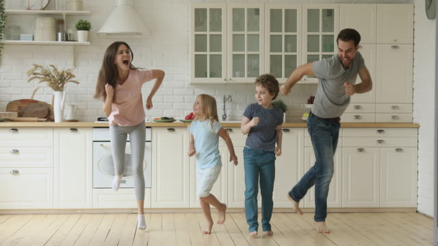 mutlu aktif ebeveynler ve sevimli çocuklar mutfakta birlikte atlama - mutfak stok videoları ve detay görüntü çekimi